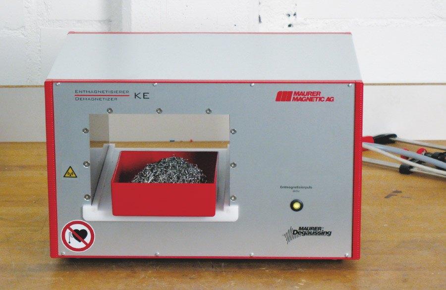 Entmagnetisierer Typ KE, im Tunnel-Entmagnetisierer befindet sich ein kleiner Behälter gefüllt mit Schüttgut für die Entmagnetisierung.