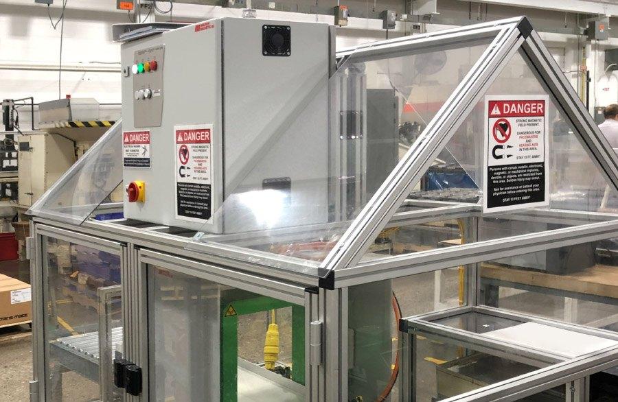 Entmagnetisierer SE in einem Plexiglass-Schutzgehäuse mit integrierterm Leistungsmodul DN1850. Der Entmagnetisier SE ist fest in der Produktionskette verbaut. Förderband bringt Kartonkisten für die Entmagnetisierung in den Tunnelentmagnetiserer.