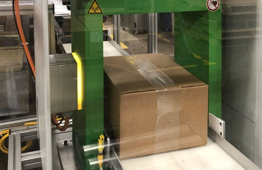 Doos met bulkmateriaal tijdens demagnetisatie in tunneldemagnetisator SE met afschermkamer. Volledig geautomatiseerd demagnetiseringssysteem met lichtschermen.